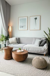 A living room with two wood coffee tables, two plants on either side of the couch, and two wall hanging photos, all in similar tones of gray.