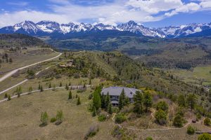 Drone shot of home with mountain views in background; useful for real estate marketing materials.