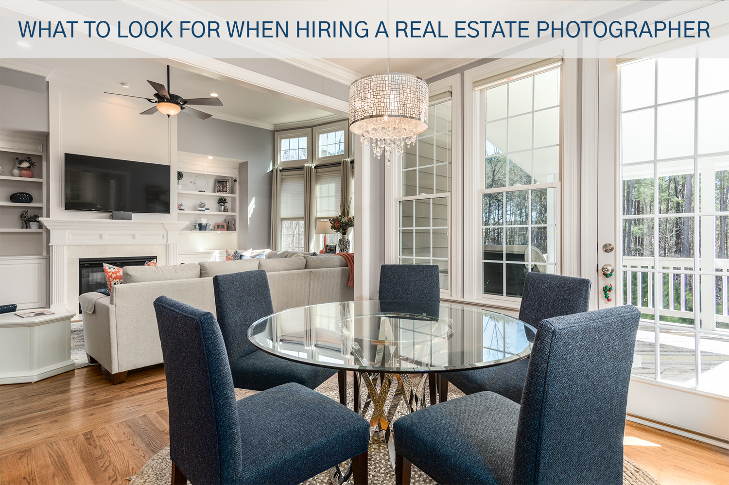 A real estate photo of a round dining table with chairs, and a living room beyond that. Shot taken by a real estate photographer.