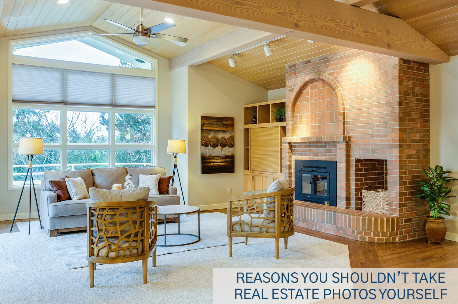 A staged living room with a brick fireplace and floor to ceiling windows.