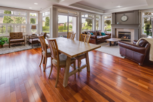 A living room with brown wood flooring, leather couches, and dining table set.