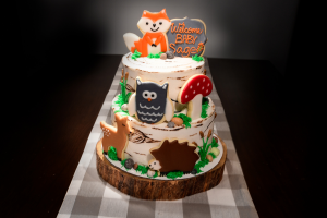Cake with forest animals sitting on a wood cake holder.